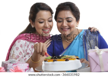 Woman cutting birthday cake while daughter looks on - stock photo