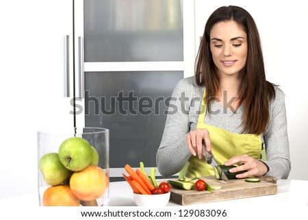 Woman cutting cucumber and vegetables in kitchen - stock photo