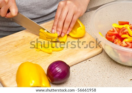 woman cutting peppers for a greek salad - stock photo