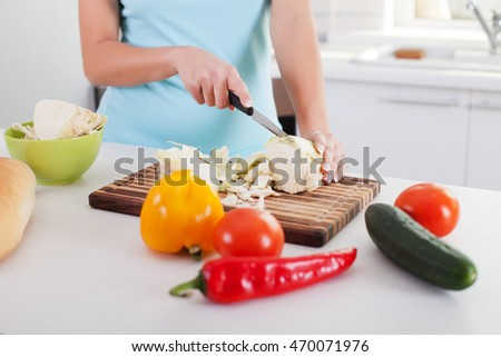 Woman cutting vegetables in modern kitchen.