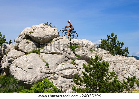 Woman cycling in the mountains - stock photo