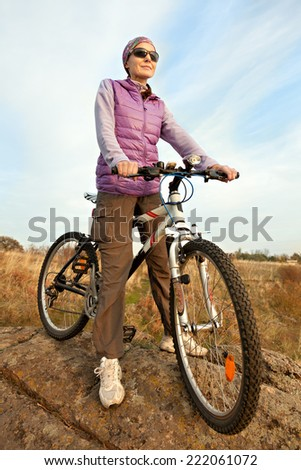 Woman cyclist stopped on a hill and looking into the distance - stock photo