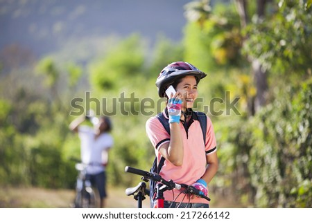Woman cyclist talking with phone . man drinking in the background