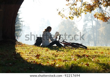 Woman cyclist with read the map sitting on halt  illuminated by the rays of bright sunlight among the green nature - stock photo