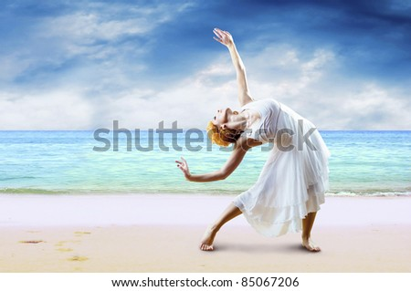 Woman dancer posing on the beach - stock photo