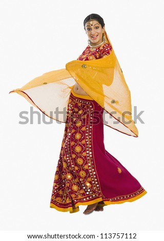 Woman dancing in bright red lehenga choli