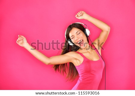 Woman dancing listening to music in headphones from smart phone or mp3 player. Sexy happy young woman dancing excited on pink background. Female model of mixed ethnicity, Asian Chinese and Caucasian. - stock photo