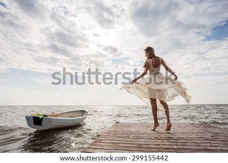 woman dancing on pier at sunrise