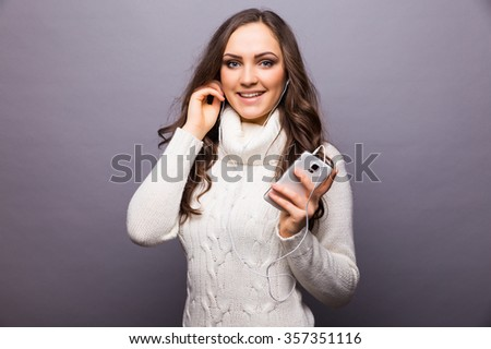 Woman dancing to music listening to phone  with earphones / earbuds. Caucasian  in white sweater isolated on grey background. - stock photo
