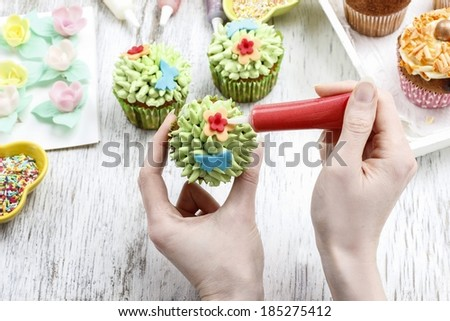 Woman decorates easter cupcakes - stock photo