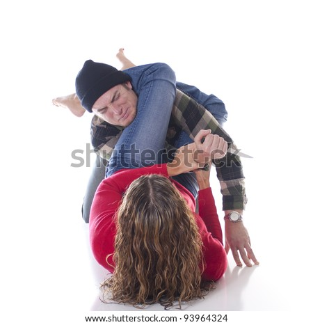 Woman defending herself against a mugger with a Jiu-Jitsu arm bar - stock photo