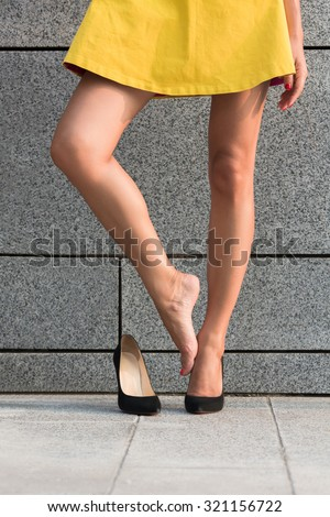 Woman demonstrating her legs in full length isolated on brick wall backround. Lady in yellow dress wearing blackhigh heels. She put off right heel to have a rest. - stock photo