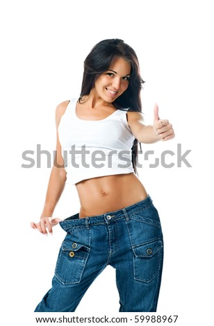 Woman demonstrating weight loss by wearing an old pair of jeans