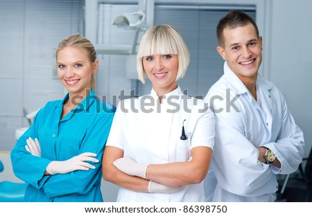 woman dentist standing in office with her personal assistants crew - stock photo