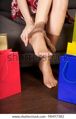 woman detail sitting on a brown sofa between shopping bags - stock photo