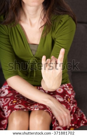 woman detail sitting on a brown sofa gesturing fuck off