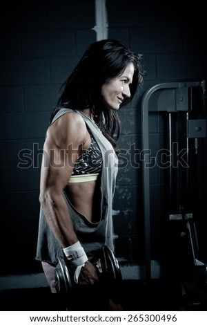 Woman determined with barbells in the gym - stock photo