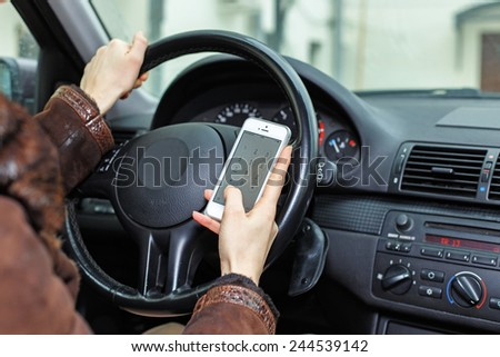 Woman dialing a number during driving a car. - stock photo