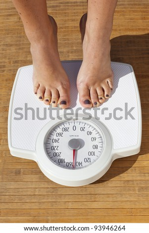 Woman Dieting, close up of woman's bare feet standing on a weight scale - stock photo