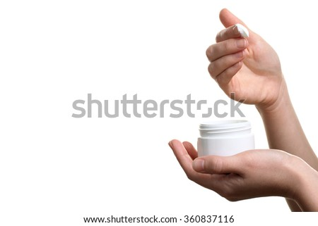 Woman dipping finger into moisturizer cream on white isolated background - stock photo