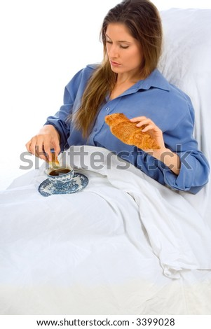 Woman dips croissant in her coffee in the bed - stock photo