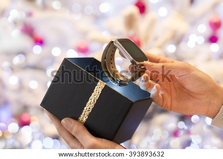 Woman discovers a smartwatch in Christmas present. Boke christmas tree background - stock photo