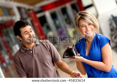 Woman displaying her man's empty wallet at a shopping center