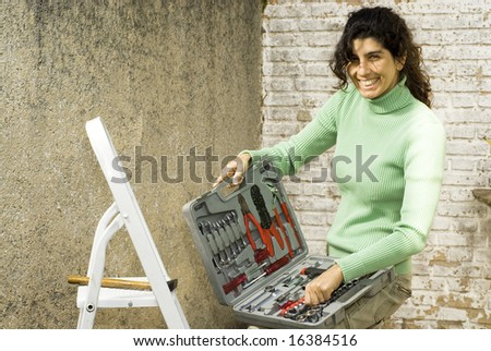 Woman displays toolkit next to ladder. She is smiling at camera. Horizontally framed photo. - stock photo