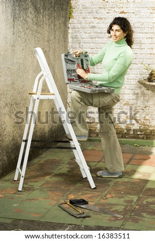 Woman displays toolkit while resting foot on ladder. She is smiling at camera. Vertically framed photo. - stock photo