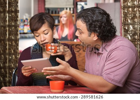 Woman distracted with tablet while man tries talking to her - stock photo