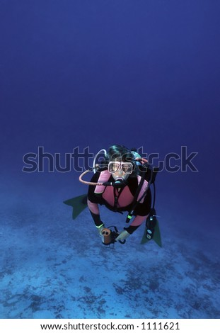 Woman diver surfacing from dive - stock photo