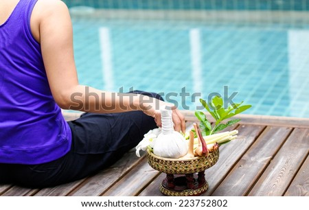 Woman do meditating with the Herbal compress ball for spa treatment - stock photo