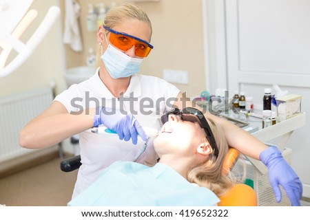 Woman doctor dentist at her working place successfully treating tooth to her patient - stock photo