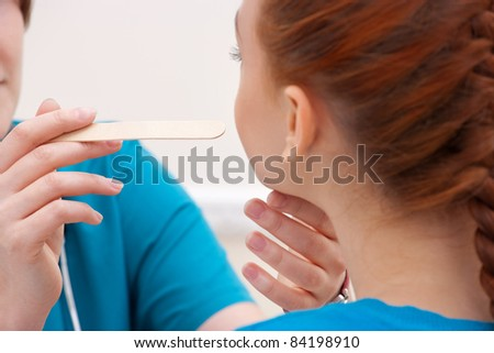 Woman doctor examines a throat of young woman