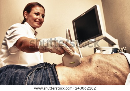 Woman doctor examining patient with abdomen ultrasound. - stock photo