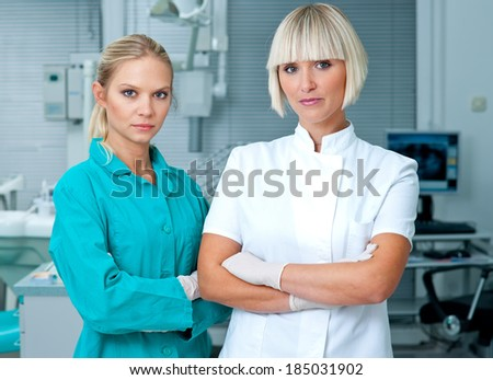 woman doctor gynecologist or oncologist with her assistant  in her office - stock photo