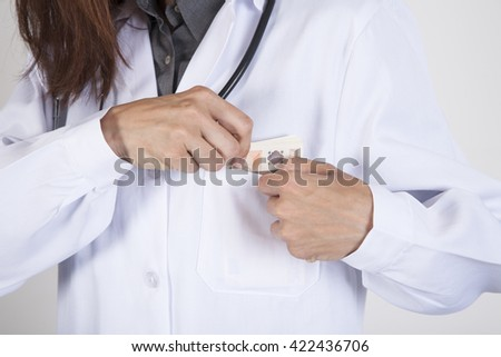 woman doctor hands with white gown and stethoscope tucking a wad of Euro banknotes in her pocket - stock photo