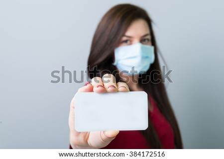 Woman doctor holding a blank white business card with copy space and advertising area - stock photo