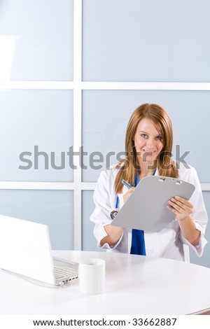Woman doctor holding a chart in a modern office - stock photo