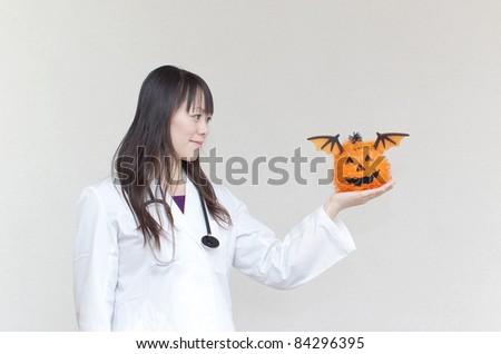 Woman doctor holding a pumpkin - stock photo