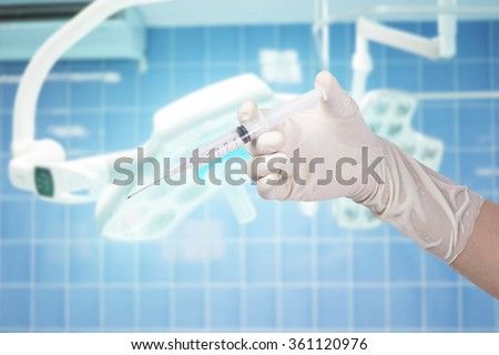Woman Doctor holding syringe on surgical room background - stock photo