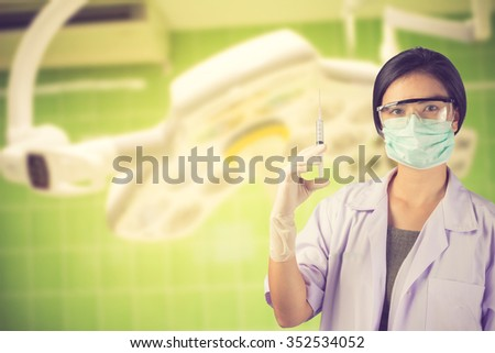 Woman Doctor holding syringe on surgical room  background vintage color - stock photo