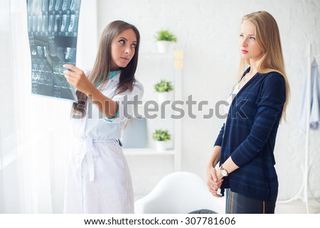 Woman doctor in hospital looking at x-ray film healthcare, roentgen, people and medicine concept - stock photo