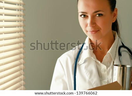 Woman  doctor is standing in the office near window with folder and holding cup - stock photo
