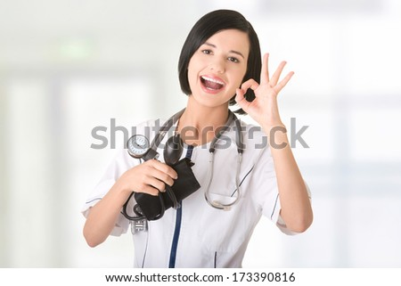 Woman doctor with blood pressure gauge gesturing perfect - stock photo