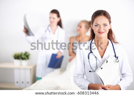 Woman doctor with folder standing at hospital