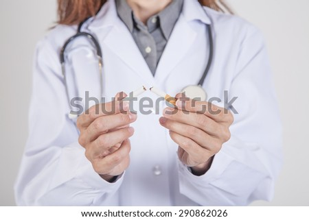 woman doctor with white gown and stethoscope breaking a cigarette tobacco in her hands over white background - stock photo