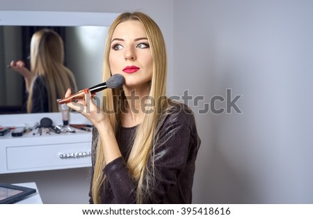woman does makeup before a mirror - stock photo