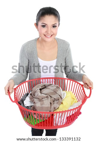 woman doing a housework holding basket of laundry - stock photo