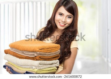 woman doing a housework holding laundry and smiling - stock photo